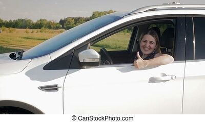 Slow motion footage of young woman driving a car and showing...