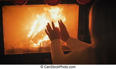 Slow motion footage of young woman in white woolen jumper warming at burning fireplace at night