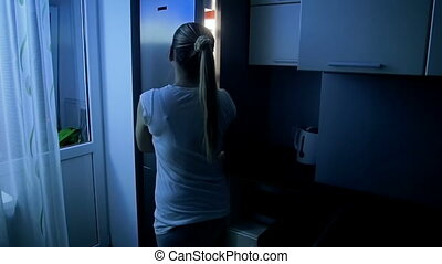 Slow motion footage of young woman open refrigerator at night