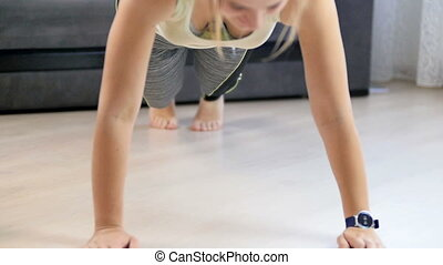Slow motion footage of young woman setting and using smart watch before doing push-ups on floor