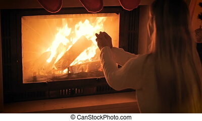 Slow motion footage of young woman sitting by the burning fireplace and warming her hands