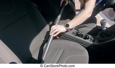 Slow motion footage of young woman cleaning passenger seat...