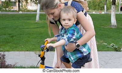 Slow motion footage of young woman teaching her toddler son riding bicycle at park