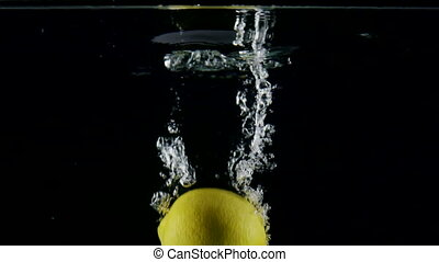 Slow motion fresh lemon falling in the splashes of water on black background