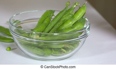 SLOW MOTION: Fresh raw green pea pods falling into a glass bowl