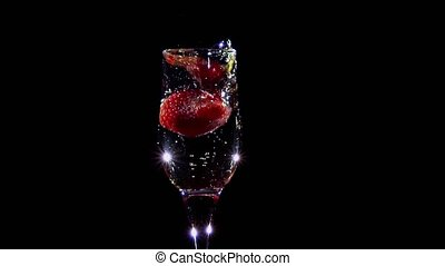 Slow motion. Fresh strawberry falling in glass with champagne wine