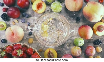 Slow motion fruit drink with ice in a glass top view