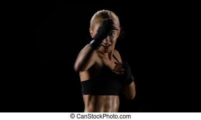Slow motion. Girl boxer training herself in a dark studio