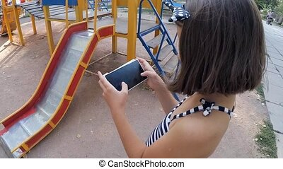 SLOW MOTION. Girl playing on a smartphone in the park