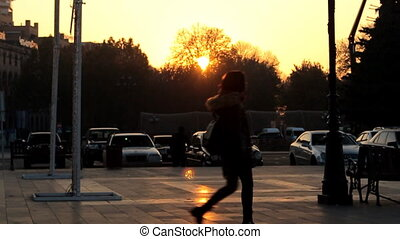 Slow Motion. Girl walking on the background golden sunset in the city