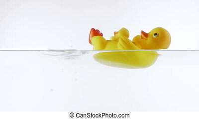Slow motion green sea bath salt falling into the water with yellow rubber duck
