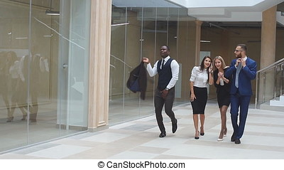 Slow motion. Group confident positive businesspeople exulting of winning. Business people walking along office corridor and celebrate the victory