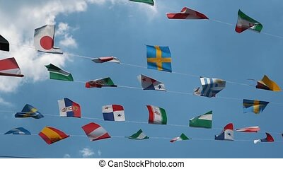 Slow motion, group of nationals flags at blue sky with white clouds. Flags of many countries of the world in the air