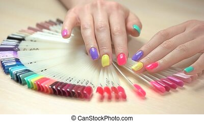 Slow motion hands choosing nail color. Beautiful female...