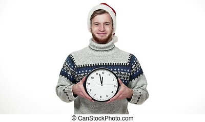 Slow motion handsome man in sweater holding clock showing time to camera.