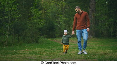 Slow motion: Handsome young man and his cute little son are walking in forest and talking enjoying fresh air, nature and communication. Family, fatherhood and tourism concept.