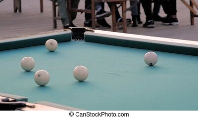 Slow motion: hitting pool ball on teal billiards table - close up view. Sport, game, competition, hobby, leisure time concept