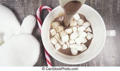 Slow motion hot chocolate pour into a mug of marshmallow top...