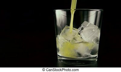 Slow motion. Ice with vodka in a glass to pour the juice