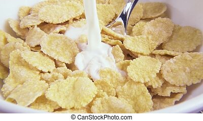 Slow motion in corn flakes pour milk close-up