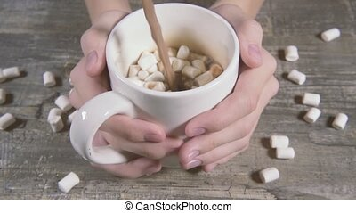 Slow motion in the hands of a white mug with marshmallows and pouring cocoa