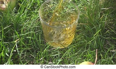 Slow motion juice is poured into a glass on the grass