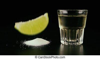Slow motion. Lime slice falls on salt