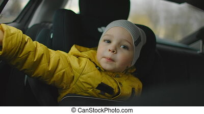 Little Boy Travelling In A Car. 2 year old Caucasian boy looking out of car window. A Two Year-Old Caucasian Boy a Seatbelt Sits in His Carseat and Looks out the Window of a Moving Vehicle.
