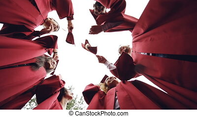 Slow motion low angle shot of graduates standing in circle...
