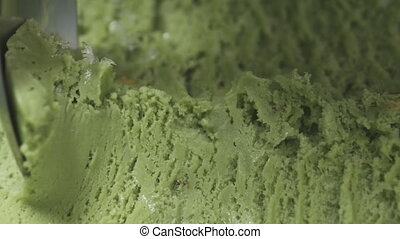 Slow motion macro of pistachio ice cream being scooped with spoon, 60fps footage