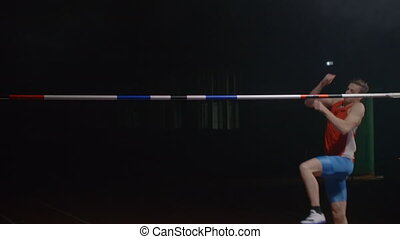 Slow motion: Male high jumper jumping over the bar and failure, error, hit the crossbar.