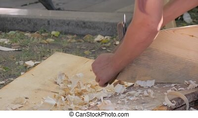 Slow motion: man carpenter using vintage plane to shape and smooth wooden board at summer historical festival - close up side view. Craftsmanship, handwork, woodworking concept