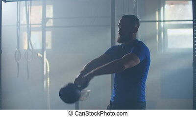 Slow motion: Man doing exercise with kettlebell in gym. fitness athletes men training muscular bodybuilders using kettlebell weights doing intense strength exercise in gym.