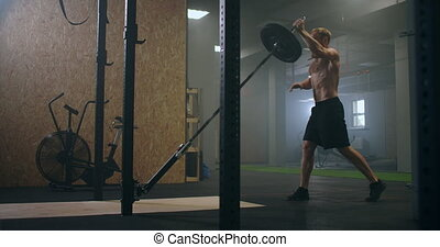 Slow motion: Man doing Single-Arm Landmine Squat-to-Press exercise. Young man lifting barbell with light weights at gym