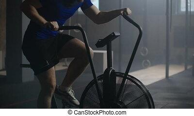 Slow motion Man exercising on air bike in gym.