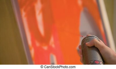 Slow motion: man hand painting colorful graffiti on wooden surface - close up