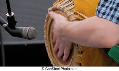 Slow motion: man hands playing ethnic Indian percussion drum mrdanga on stage of summer open air concert - close up view. Entertainment, music, culture, leisure time and art concept