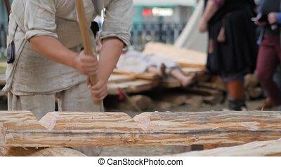 Slow motion: man lumberjack cutting large log with axe at ...