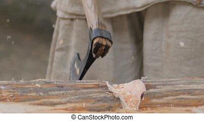Slow motion: man lumberjack cutting large log with axe - wood shavings, chips flying at summer historical medival festival - close up. Craftsmanship, reenactment, handwork, revival concept