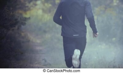 Slow motion. Man running away into foggy forest. Escaping...