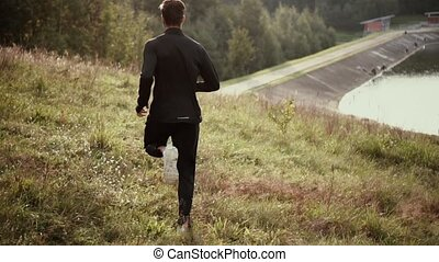 Slow motion. Man running down fall grass hill. Camera...