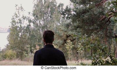 Slow motion. Man running through deep woods. Camera follows...