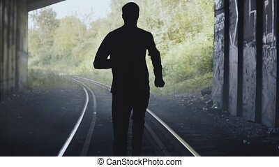Slow motion man silhouette running on train tracks. Back view. Abstract background ending shot. In pursuit for freedom.
