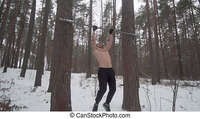 Slowmotion almost failed Muscle up attempt. Man working out on outdoors forest sports ground. Young athlete performing street workout warm up. Calisthenics training. Freezing cold winter weather. Slowmo