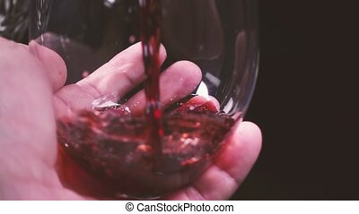 Man's hand rotates a glass of wine