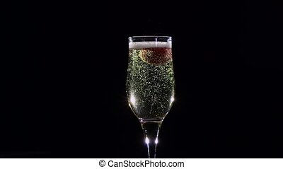 Slow motion. Mellow strawberry in glass with champagne sparkling wine