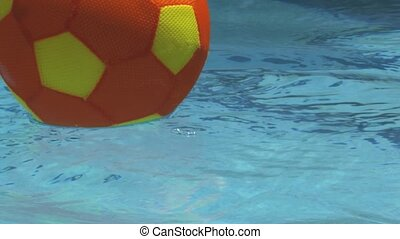 Extreme slow motion of a summer ball landing in the pool