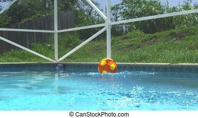 Shot in slow motion of a ball landing in a swimming pool