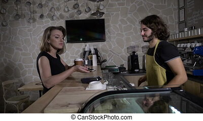 Slow motion of a barista male serving coffee to go while the...