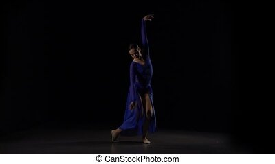 Slow motion of a glorious ballerina in purple dress dancing elements of a modern ballet in the twilight over a black background of studio. Girl with a beautiful slim figure.